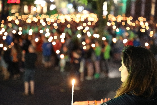 Ein Bild vom Abend der Begegnung auf dem 37. Deutschen Evangelischen Kirchentag, bei dem viele bunte Menschen mit brennenden Kerzen zu sehen sind.